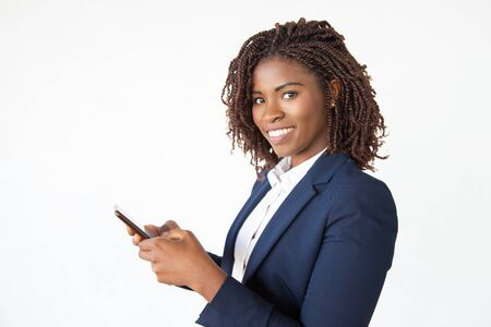 Smiling successful professional using mobile phone, texting message. Young African American business woman standing isolated over white background. Communication concept Imagens