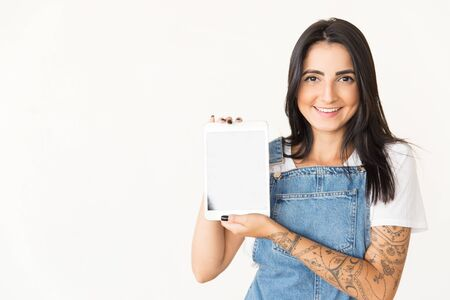 Cheerful woman showing tablet pc. Beautiful happy young woman holding digital tablet with blank screen and smiling at camera on white background. Technology concept