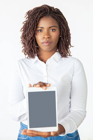 Positive confident tablet user showing blank screen, presenting new app or software. Young African American business woman standing isolated over white background. Wireless internet concept
