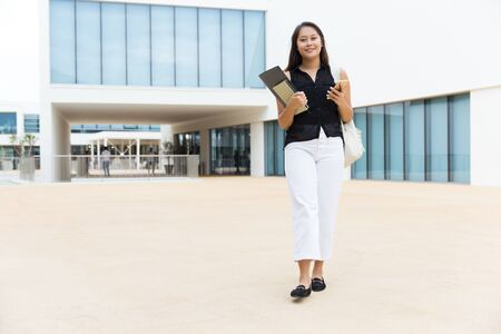 College student with books and cell phone. Full length view of attractive smiling young woman holding books and using cell phone while walking on street. Education and technology concept