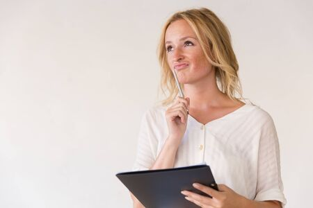 Pensive young woman holding pen and folder with paper. Beautiful blonde woman in casual standing isolated over white background, looking at copy space away. Paperwork concept