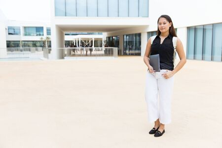 Confident young female colleague student. Full length view of beautiful young woman with backpack holding folder with pencil and looking at camera. Education concept