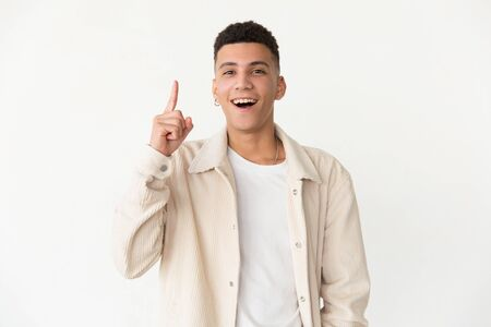 Content man with open mouth. Cheerful young man pointing up with finger and having idea, looking at camera. Idea concept Stock Photo