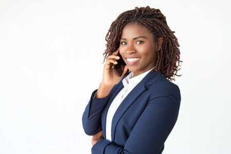 Happy successful consultant talking on mobile phone, looking at camera. Young African American business woman standing isolated over white background. Business communication concept Reklamní fotografie