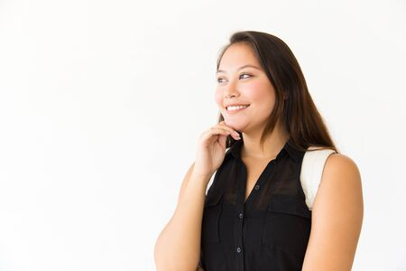 Cheerful smiling student girl touching chin and looking at copy space away. Young Latin woman in casual standing isolated over white background. Advertising concept Stock Photo