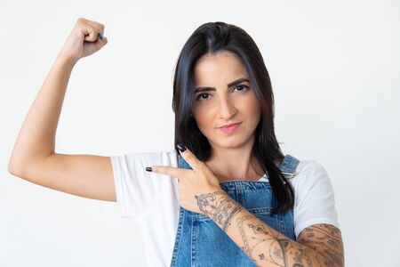Serious young woman pointing at arm. Focused lady showing muscles on white background. Concept of sport