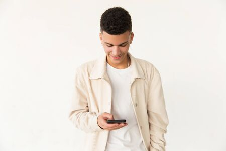Smiling young man using smartphone. Portrait of handsome happy young man standing and using mobile phone. Technology concept