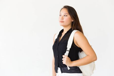 Pensive teenage girl wearing backpack, looking at copy space near her. Young Latin woman standing isolated over white background. Teenage portrait concept