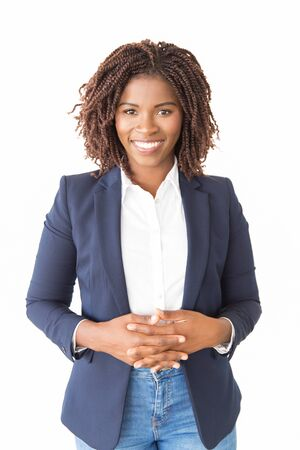Happy joyful female agent posing with clasped hands. Young African American business woman standing isolated over white background, looking at camera. Successful professional concept