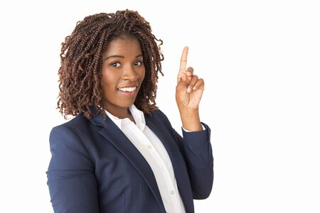 Joyful young professional having new idea, pointing index finger up. African American business woman standing isolated over white background, looking at camera, smiling. Advertising concept Stock Photo