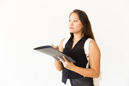 Serious young woman writing on folder. Beautiful young female student with backpack holding folder with pen and looking aside. Education concept
