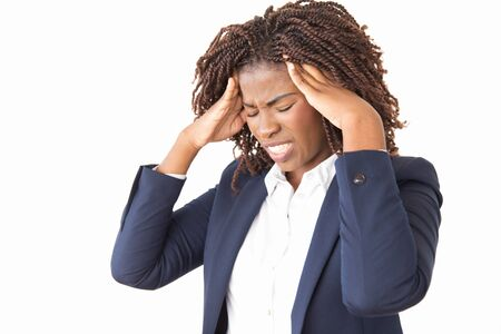 Stressed unhappy female employee suffering from headache. Young black business woman with pain face and closed eyes standing over studio background, holding head and temples. Health problem concept