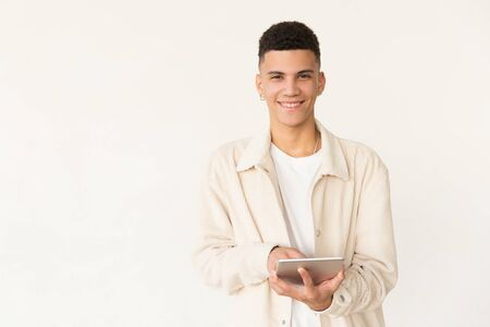 Cheerful man using tablet pc. Portrait of handsome happy young man using digital tablet and smiling at camera. Wireless technology concept