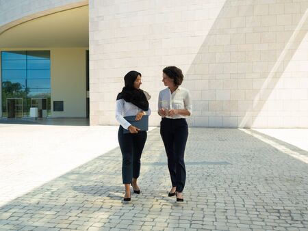 Diverse female business colleagues chatting, while going outside. Young Muslim businesswoman walking from office building, holding folder and talking to colleague. Communication concept