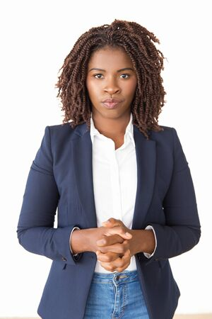 Serious female manager posing with clasped hands. Young African American business woman standing isolated over white background, looking at camera. Business leader portrait concept