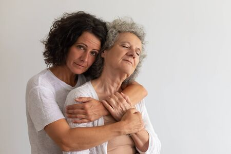 Serious adult daughter embracing senior mother in studio. Middle aged woman hugging elderly lady and looking at camera. Family portrait concept