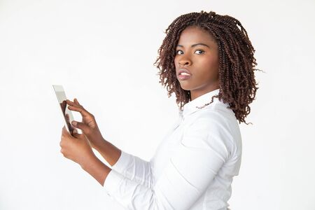 Serious professional working on tablet, using digital device, touching screen. Young African American business woman standing isolated over white background. Gadget for business concept 写真素材