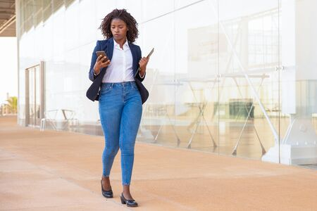 Serious female employee walking outside with cell. Young African American business woman using mobile phone, looking at screen, reading or texting message. Communication concept