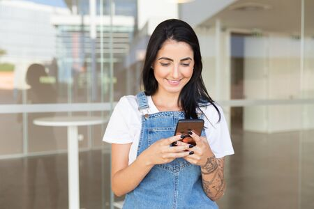 Smiling young woman using smartphone. Portrait of beautiful cheerful young woman standing on street and texting via cell phone. Communication concept