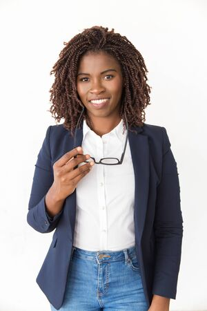 Happy cheerful expert holding glasses. Young African American business woman standing isolated over white background, looking at camera. Corporate portrait concept