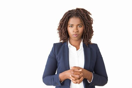 Serious female business leader posing with clasped hands. Young African American business woman standing isolated over white background, looking at camera. Confident businesswoman concept