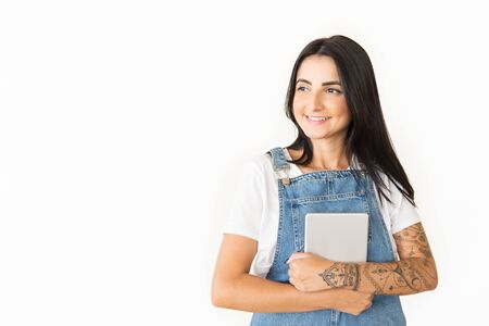 Smiling young woman with digital tablet. Beautiful young tattooed woman holding tablet computer and looking away isolated on white background. Technology concept 写真素材
