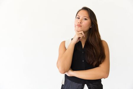 Thoughtful woman with backpack looking at camera. Portrait of beautiful pensive young woman with backpack standing with hand on chin and looking at camera on white. Facial expression concept