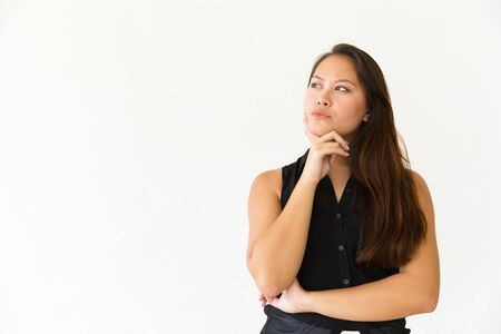 Thoughtful young woman with hand on chin. Portrait of beautiful pensive young woman standing with hand on chin and looking away on white background. Advertising concept