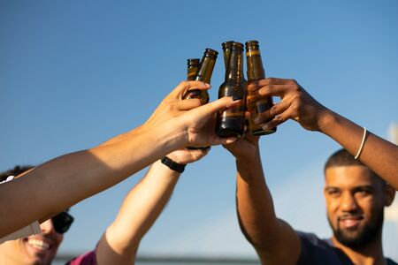 Cheerful friends clinking bottled beer outdoors. Hands of young men and women holding bottles and toasting. Outdoor party concept