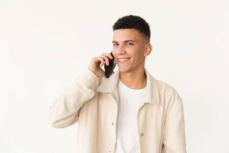 Cheerful young man talking by smartphone. Portrait of handsome happy young man talking by mobile phone and smiling at camera. Connection concept