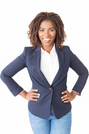 Happy female business leader posing with hands on hips. Young African American business woman standing isolated over white background, looking at camera, smiling. Successful businesswoman concept 写真素材