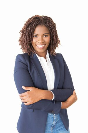 Happy successful female agent looking at camera. Young African American business woman with arms crossed standing isolated over white background, smiling. Business portrait concept