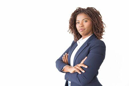 Presentación profesional acertada seria en estudio. Joven mujer de negocios afroamericana con los brazos cruzados que se encuentran aisladas sobre fondo blanco, mirando a la cámara. Concepto de confianza empresaria
