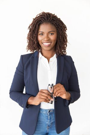 Happy cheerful manager holding glasses. Young African American business woman standing isolated over white background, looking at camera. Female portrait concept