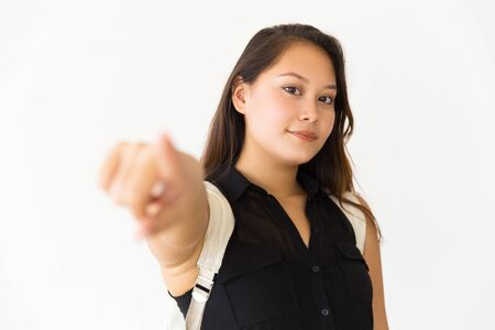 Pensive smiling teenage girl pointing finger at camera. Young Latin woman standing isolated over white background. Choosing you concept