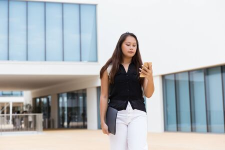 Focused female student reading message on cell. Young Asian woman walking outside, using mobile phone, looking at screen. Communication concept