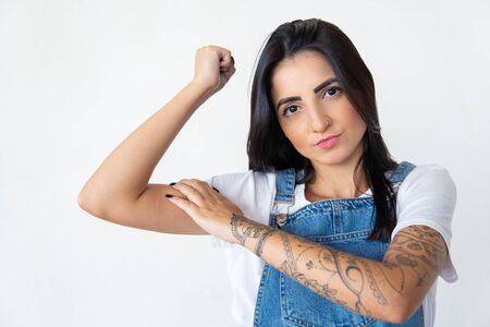 Serious young woman showing muscles. Focused lady posing on white background. Concept of sport