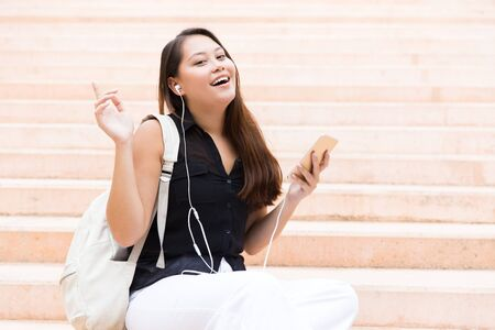 Joyful excited student girl listening to music on cell. Young Latin woman wearing earphones, sitting on outdoor stairs, holding mobile phone, smiling, looking at camera. Internet connection concept