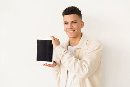 Cheerful man showing digital tablet. Portrait of handsome happy young man holding tablet pc with blank screen and smiling at camera. Technology concept