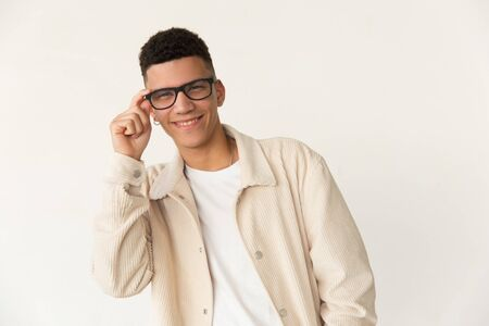 Happy man in eyeglasses looking at camera. Portrait of cheerful young man adjusting spectacles and smiling at camera. Style concept
