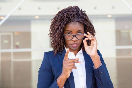 Serious businesswoman in eyeglasses shaking finger. Young African American business woman standing outside, adjusting glasses, pointing at camera. Index finger gesture concept 写真素材