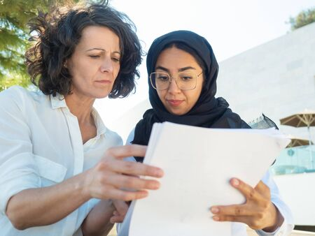 Confused female business leader showing document to expert outside. Business colleagues reading document together. Consulting concept