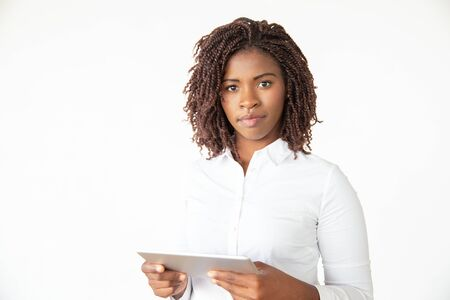 Serious confident professional holding tablet, looking at camera. Young African American business woman standing isolated over white background. Watching video concept 写真素材