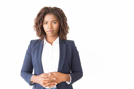Serious confident professional posing with clasped hands. Young African American business woman standing isolated over white background, looking at camera. Business portrait concept 写真素材