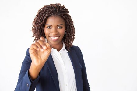 Happy friendly business trainer writing on glass board with marker. Young African American business woman standing isolated over white background. Corporate training concept