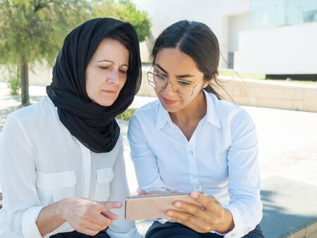 Serious excited business colleagues watching content on smartphone screen together. Muslim employee showing video on mobile phone to female coworker. Digital communication concept