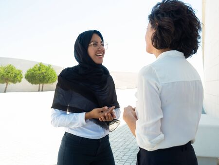 Happy excited female business colleagues discussing project outside. Young Muslim businesswoman talking to coworker and smiling. Muslim business lady concept