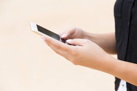 Woman using mobile phone, texting message, touching screen with fingers. Closeup of female hands holding smartphone outside. Communication concept