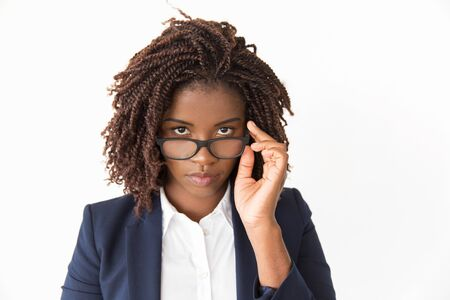 Serious office worker taking her glasses off. Young African American business woman looking at camera over eyeglasses. Isolated front over white background Vision concept