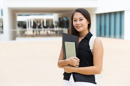Happy young woman with textbooks. Beautiful young female student holding folder with books and smiling at camera. Education concept